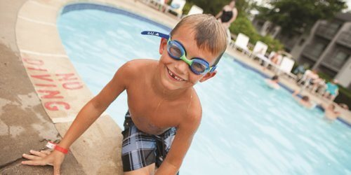 Young boy wearing goggles, sitting on the edge of an outdoor pool