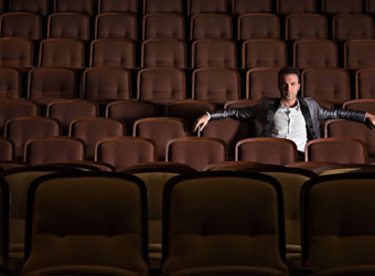 Magician Jason Hudy Sits in an empty auditorium with his arm sspread wide.