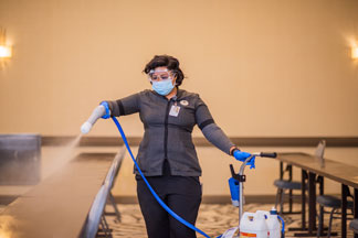 Housekeeper cleaning with a Clorox 360 sprayer