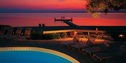 Pool with Grand Traverse Bay in background at sunset at Grand Traverse Resort and Spa's Private Beach Club